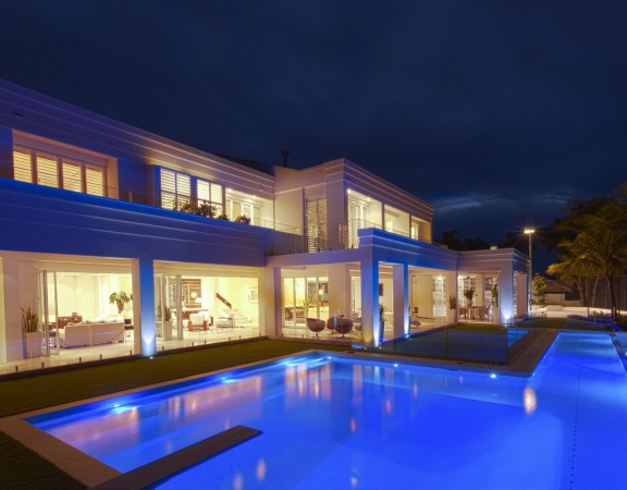Luxurious white villa with a big pool, photographed at night